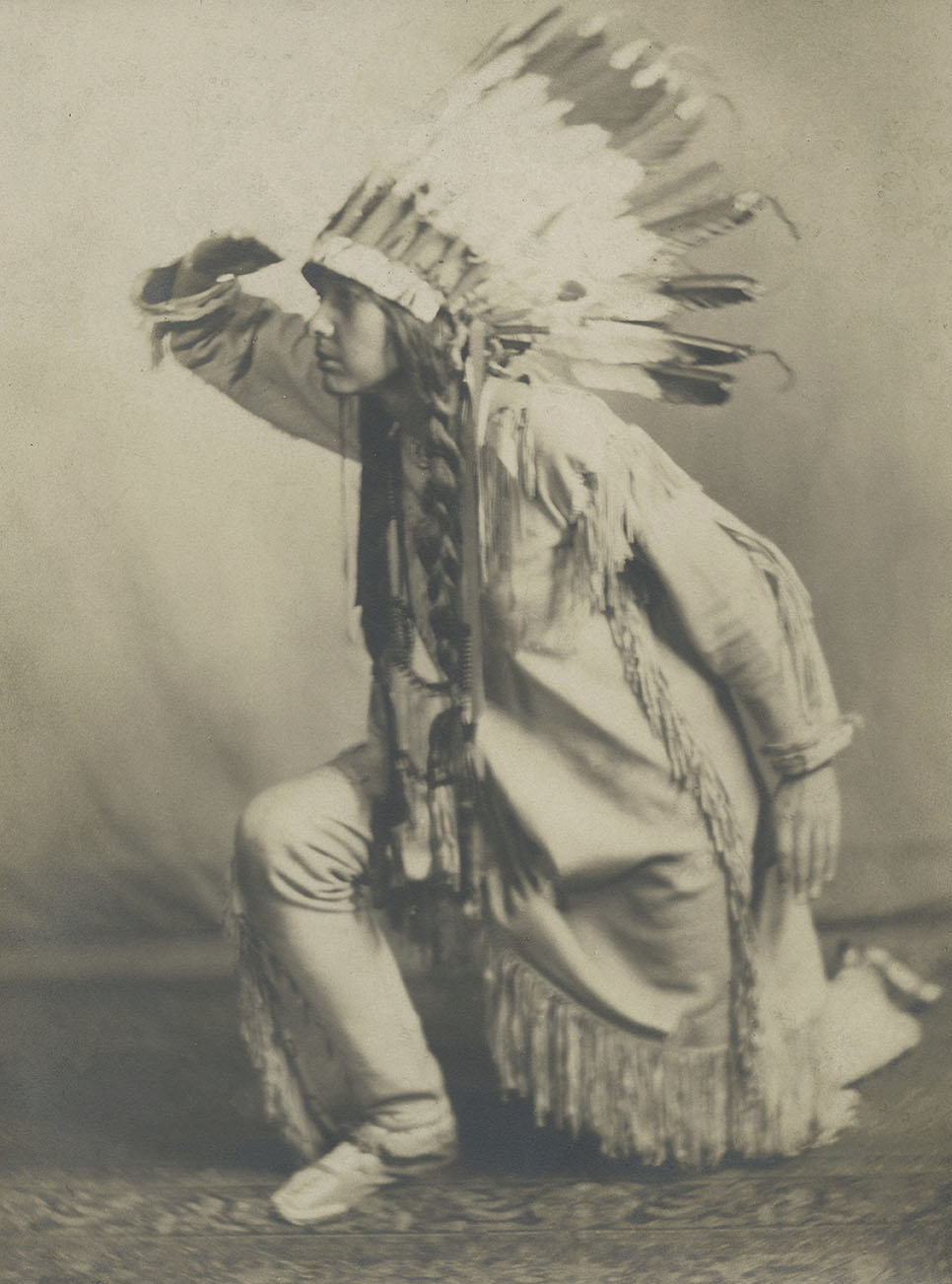 Te Ata posing in a Native American headdress.