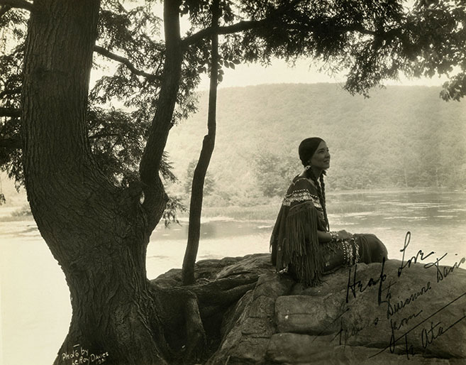 Te Ata in traditional Native American dress, sitting at shore