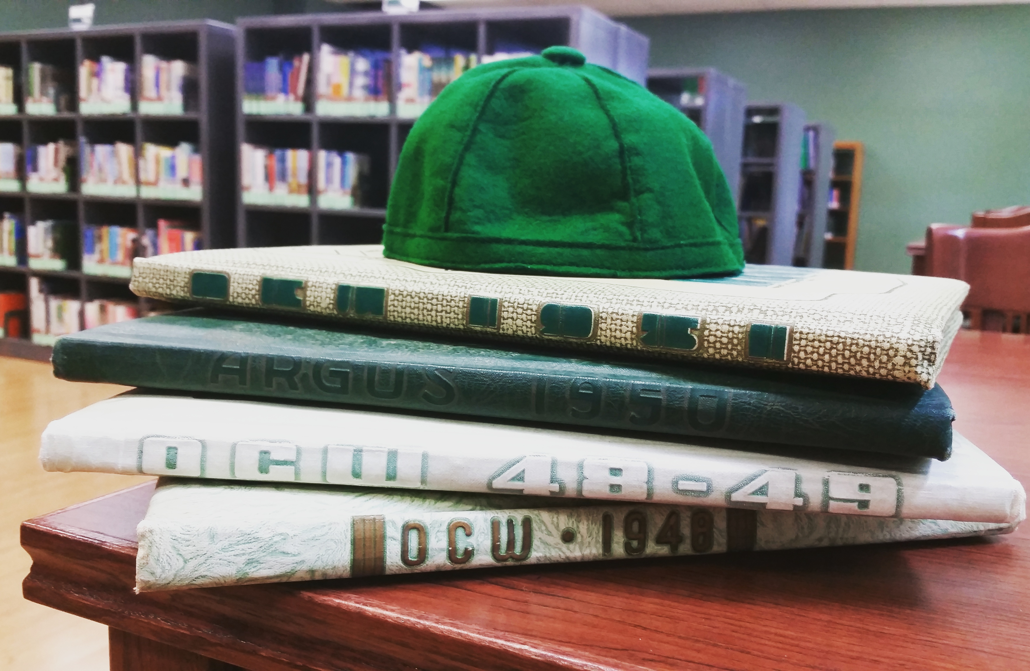 in Nash Library room 301, a green felt beanie atop a stack of four Oklahoma College for Women yearbooks