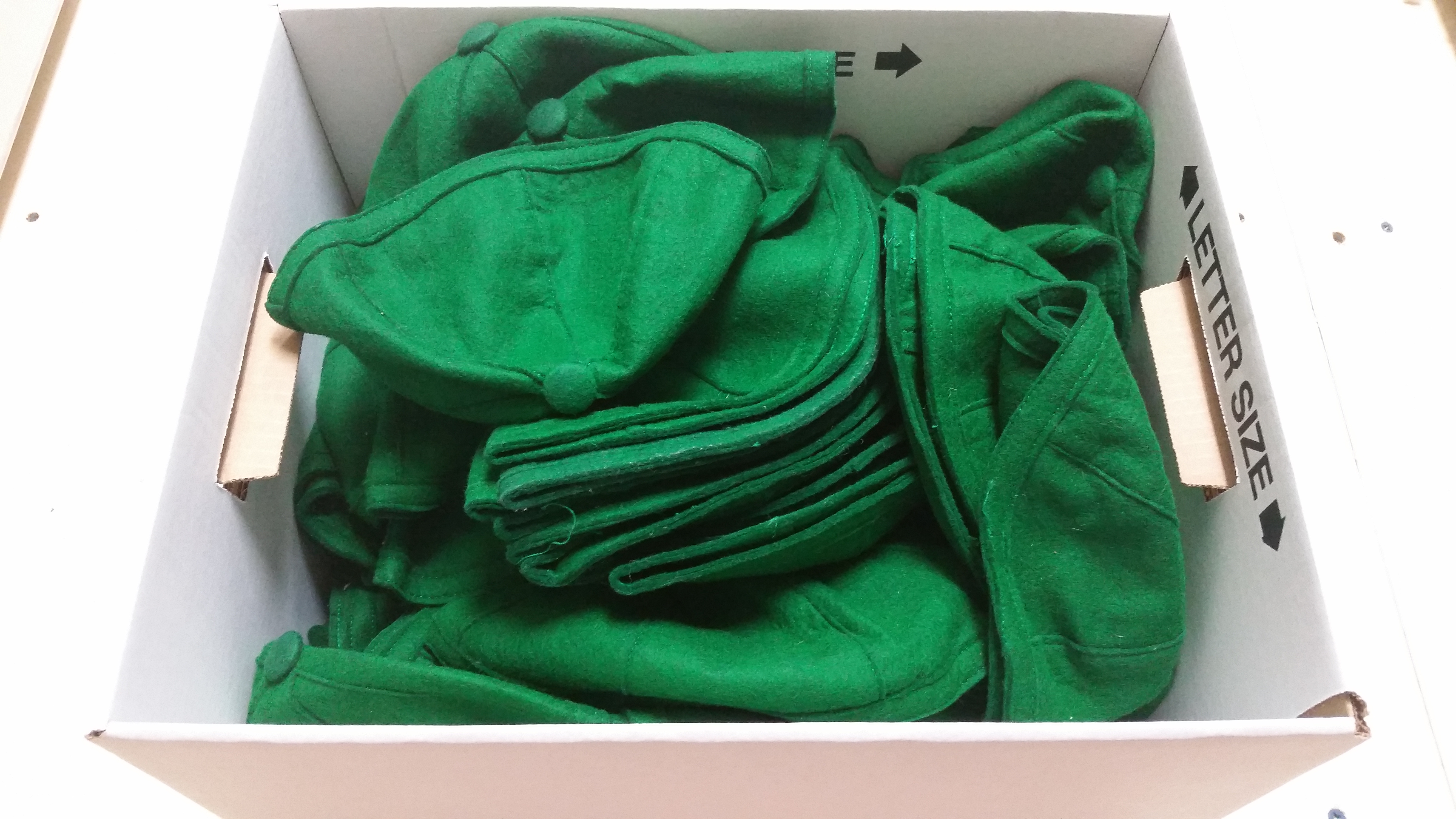 cardboard box full of green felt beanies from Nash Library archives