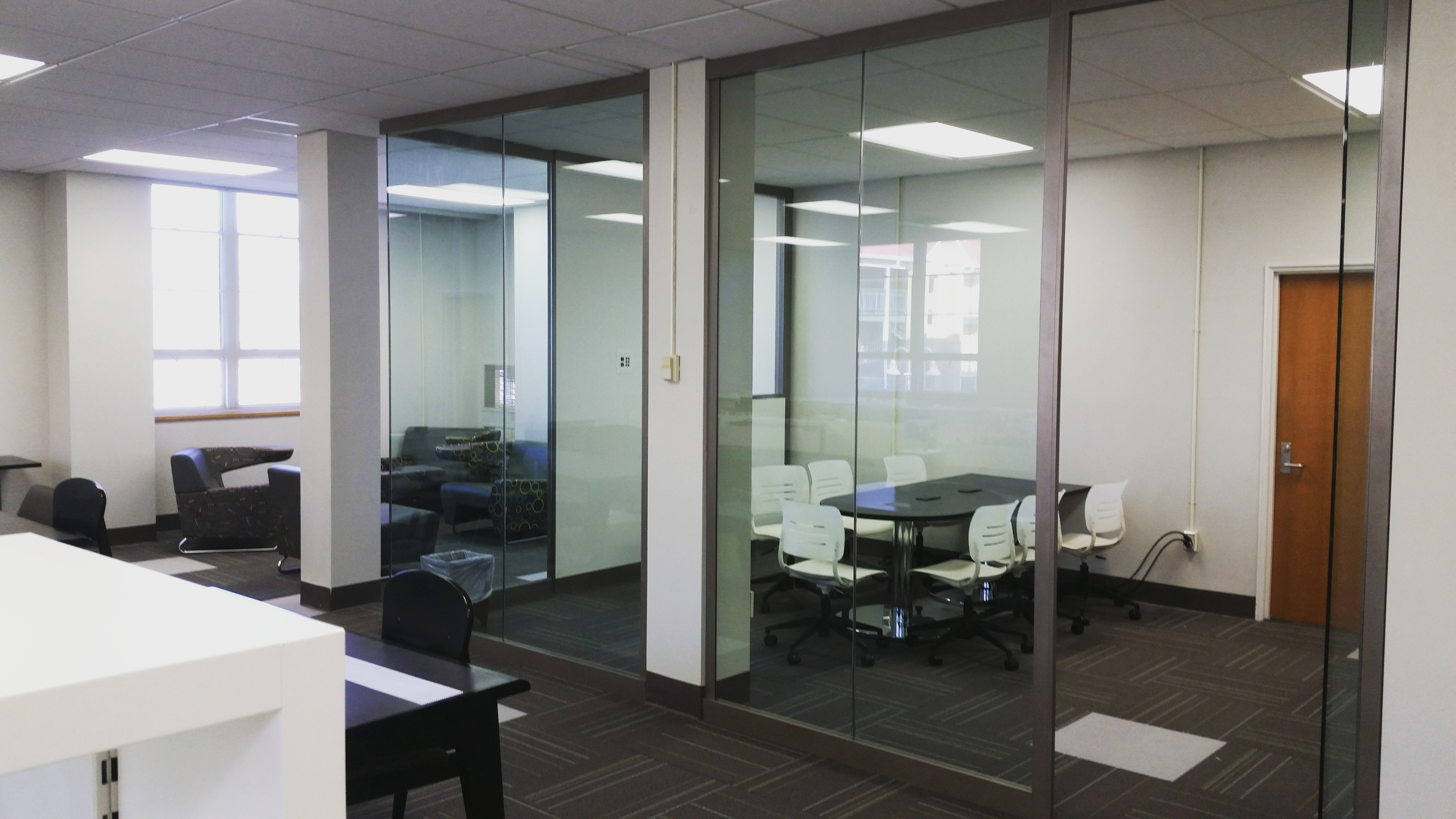 Nash Library's glass-walled classroom in music pocket library with table and chairs