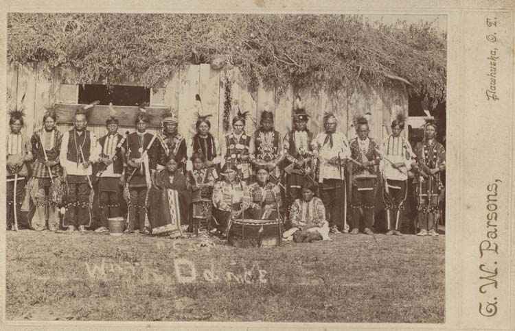A group of American Indians in costume with musical instruments